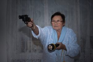 Senior-holding-guns-and-torch-for-home-defense