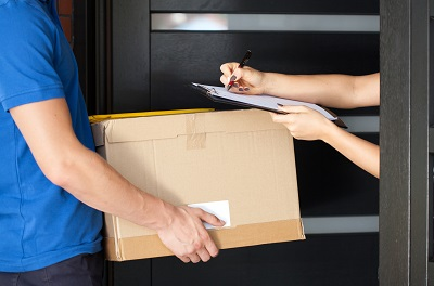 A person signing parcel delivery papers