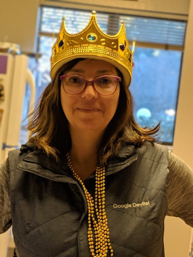 Alt text: Monica wearing a gold crown, gold beads, and a gray, Google-branded vest.