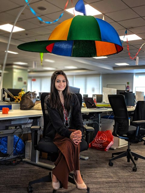 Snehal sitting at a desk with a large structure above her shaped like a colorful hat with a propeller.