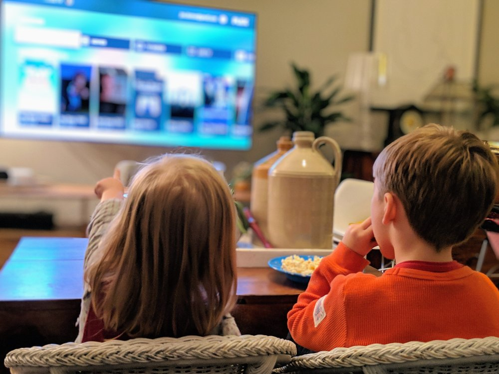 photo of two children sitting in a living room watching TV