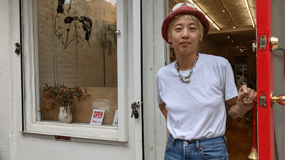 A person standing in front of a white business store-front. They're wearing a white shirt, blue jeans, a red hat, and a necklace welcoming a customer into the shop.