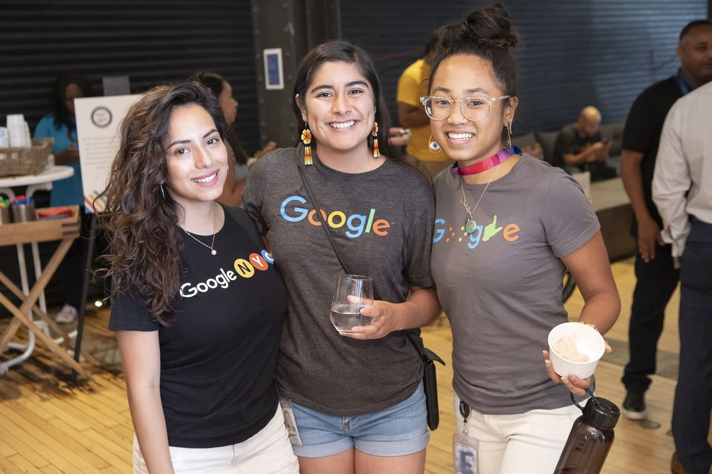 Three people wearing Google shirts at an indoor event.
