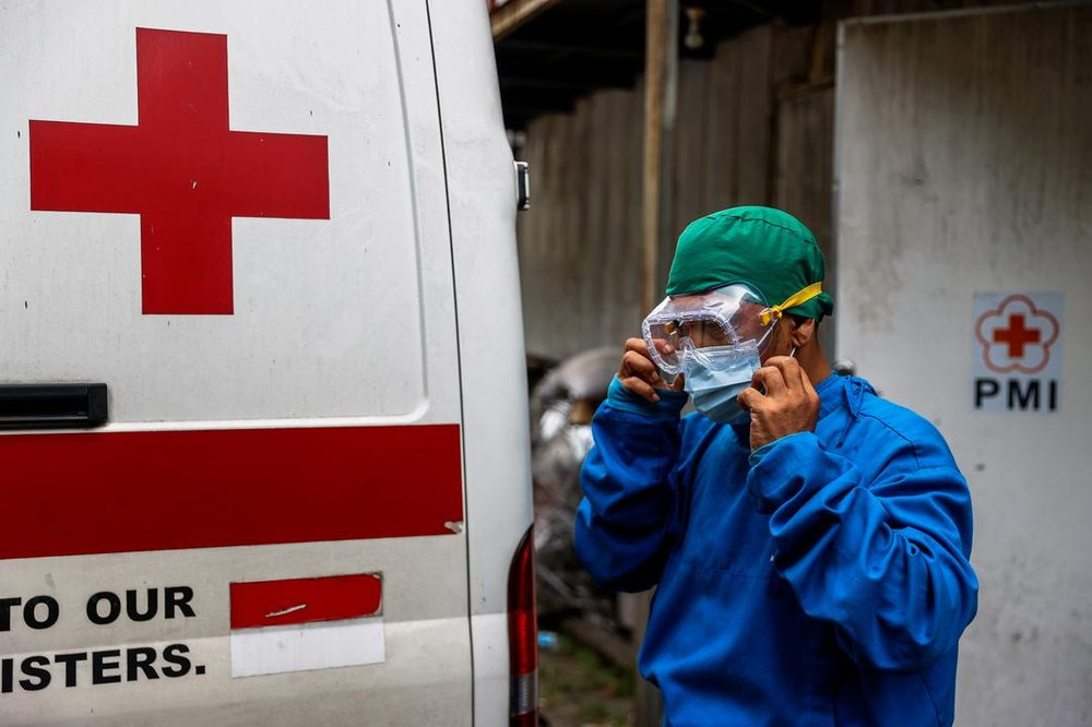 A photo of medical personnel in protective clothing and goggles next to the back of Red Cross van