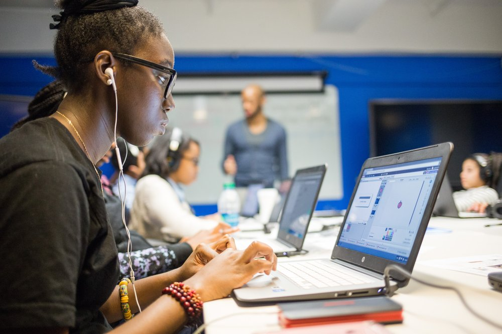 Side profile of a young Black female with headphones, actively working on a laptop