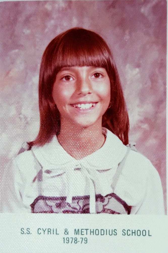 A young Monica smiling at the camera. She is wearing a white collared shirt and posing for her 3rd grade photo.