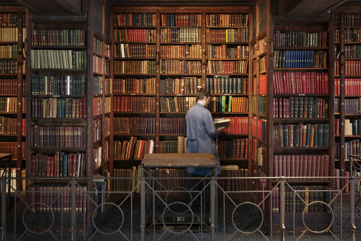 a person looks at a book in a large library filled with many volumes.jpg