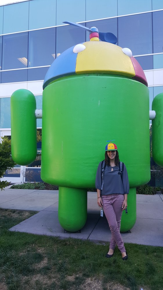 Emily standing next to a large Android statue with a Noogler hat.