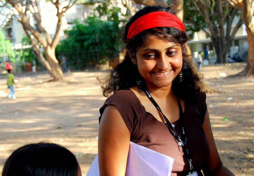 Nithya smiling at a small child while working in the field.