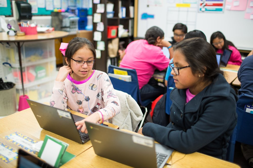 Two middle school girls share their coding projects with each other on laptops in a classroom with other students in the background.