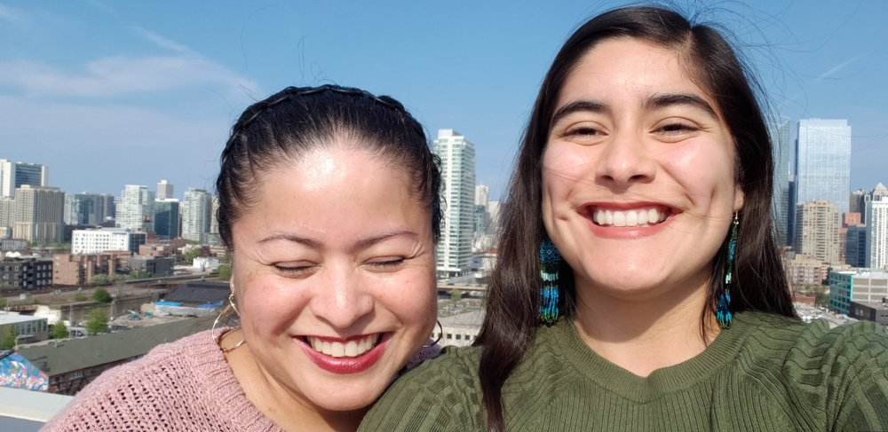 Xiomara and her mom posing on a rooftop outside.