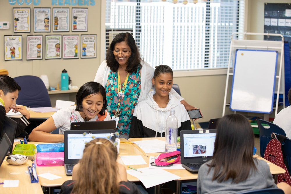 An educator works with her two middle school students on computer science lessons in the classroom.