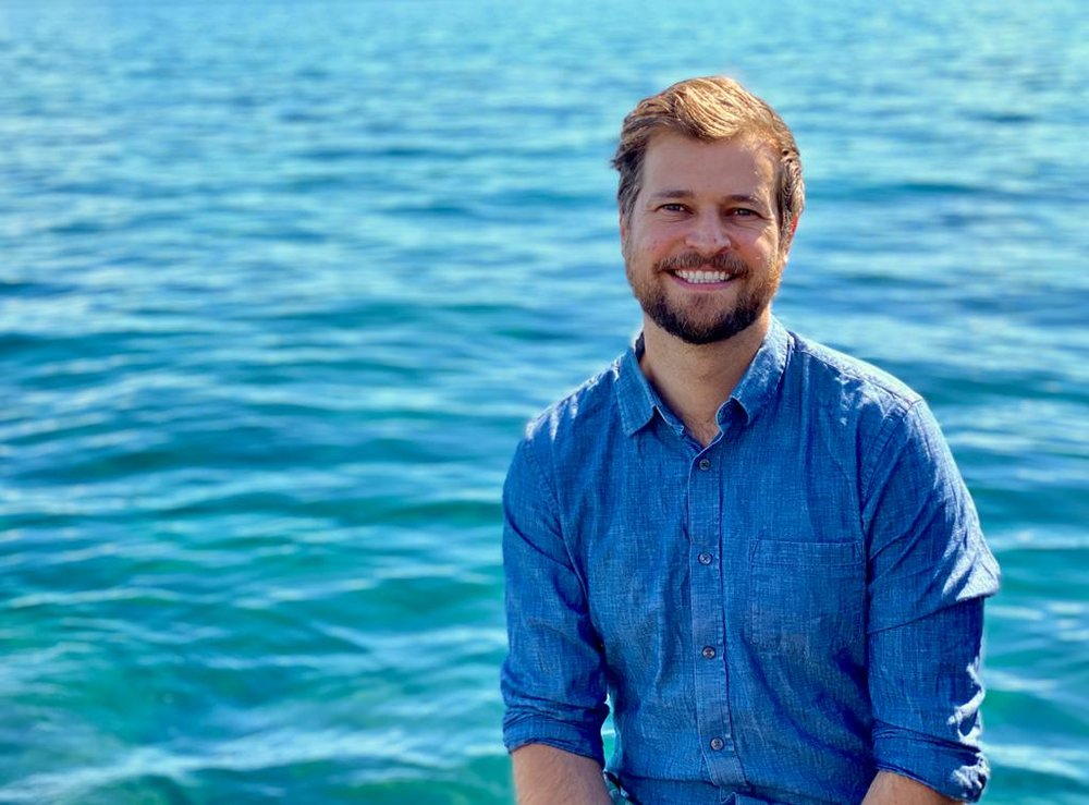 Photo shows Andreas Gyr, wearing a blue shirt, pictured against a water background, smiling at the camera.