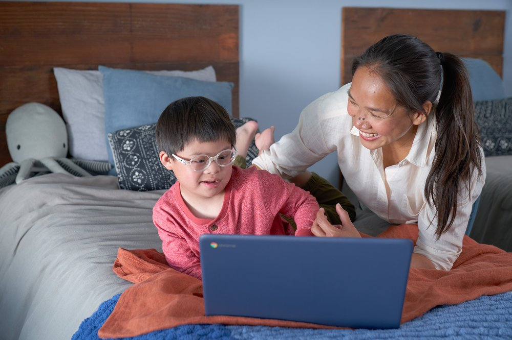 A young boy wearing glasses is lying on a bed looking at a Chromebook, with his mother next to him.