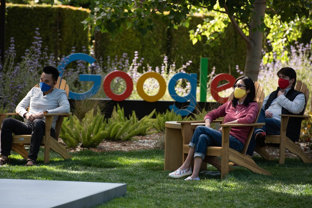 """Three masked people sit near a """"Google"""" sign in adirondack chairs on a lawn."""