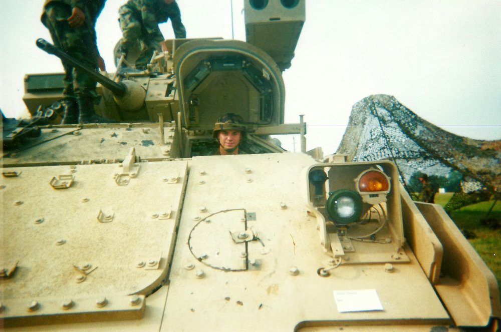 Dennis James smiling and sitting in a tan military vehicle called a Bradley Fighting Vehicle. Two other soldiers are pictured in the top-left corner standing on top of the vehicle. le's hero media