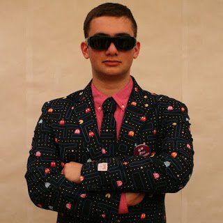 Shea standing indoors wearing sunglasses and a suit decorated with pac man figurines.