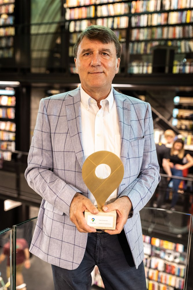 Bookshop owner Ton Harmes stands in front of bookcases holding his Golden Pin trophy from Google