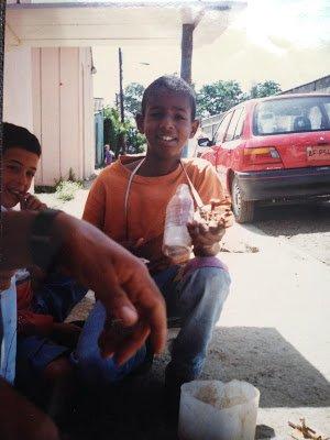 Juan as a child holding a homemade guitar.