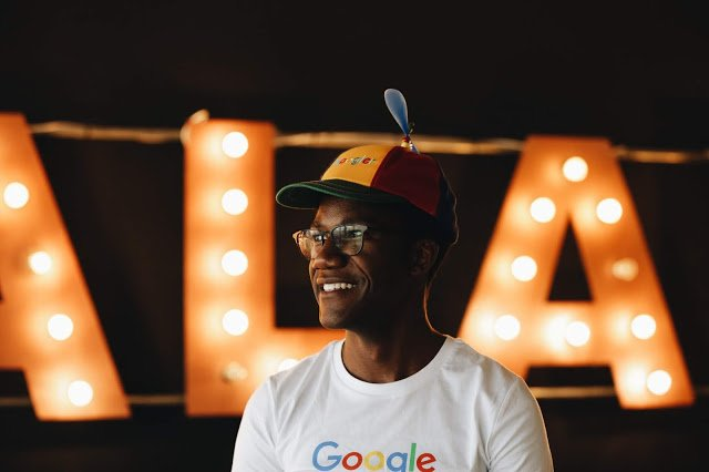 Goodman in Noogler hat and Google shirt in front of large light-up letters.
