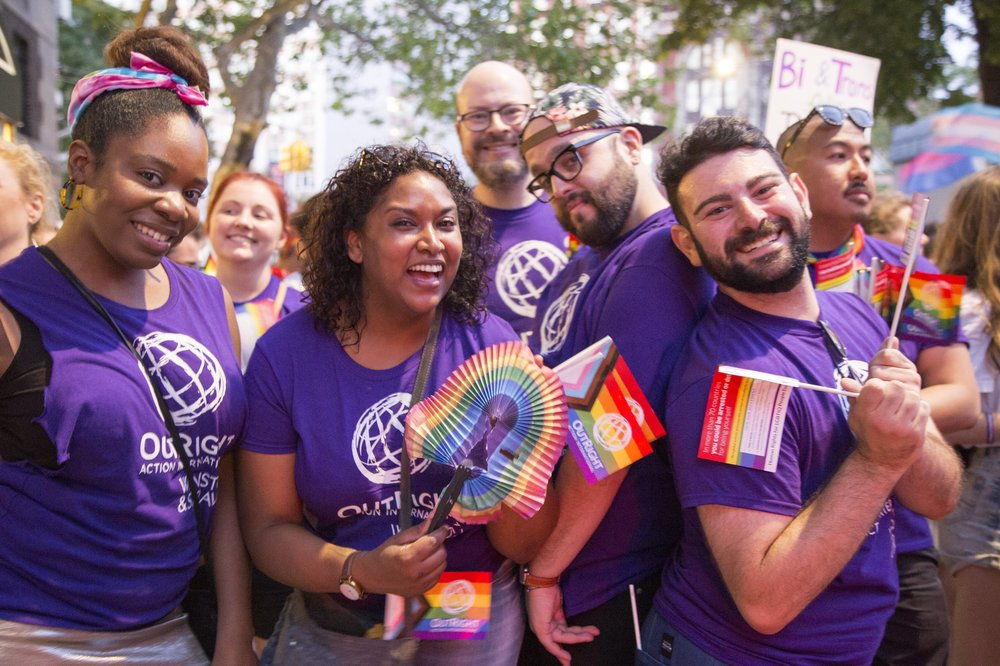 People wearing purple OutRight T-shirts and carrying Pride flag paraphernalia. Photo credit: Hanna Benavides