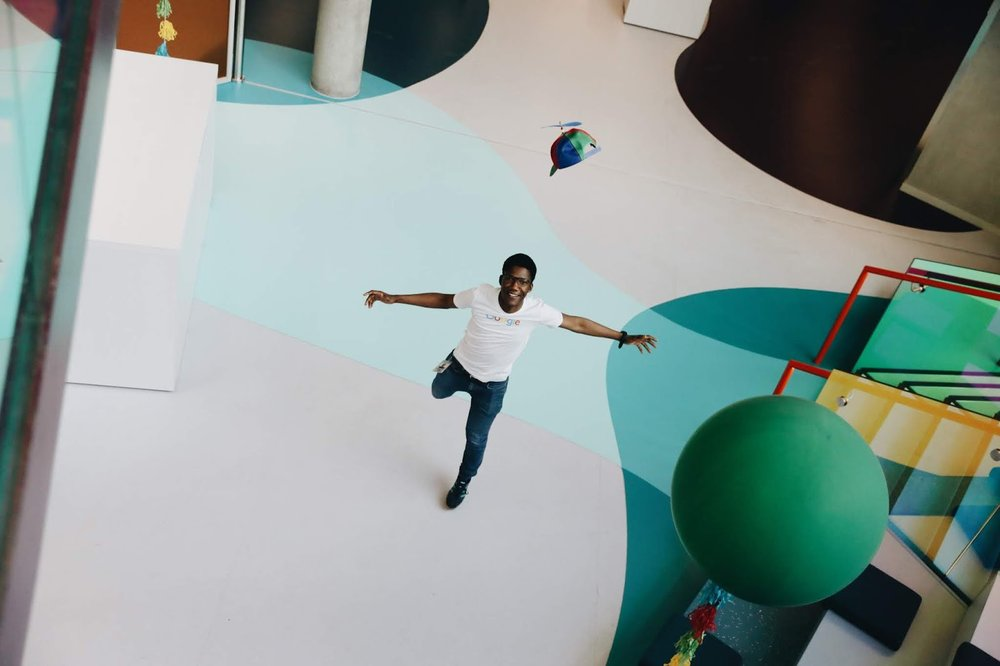 Overhead photo of Goodman tossing a hat inside a Google office.