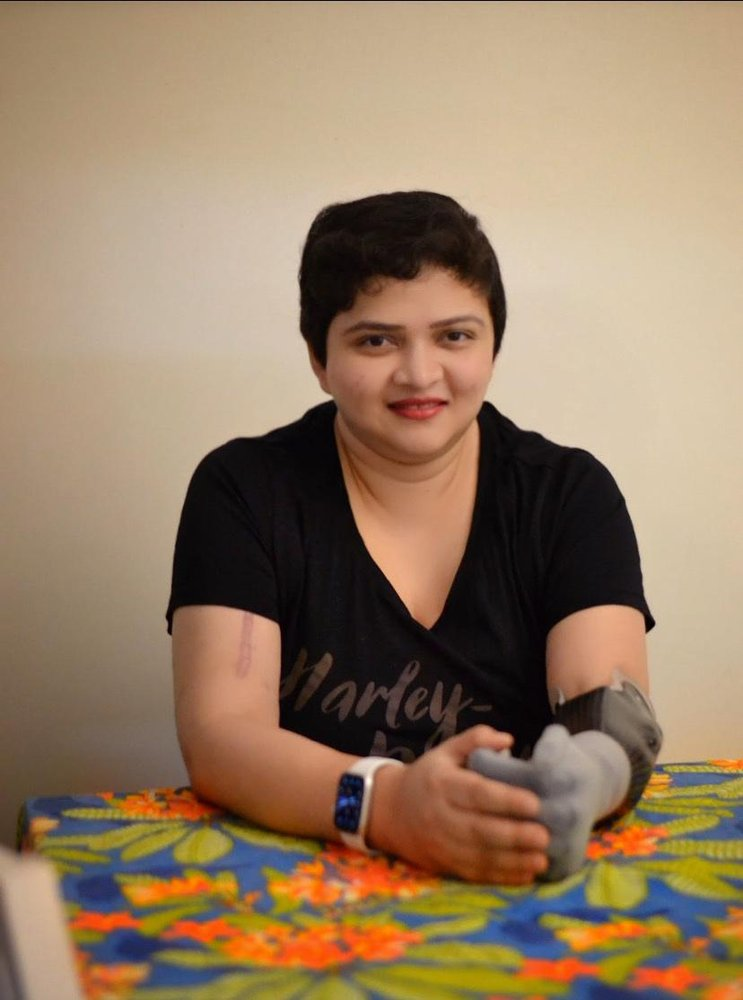 South Asian woman wearing a black shirt, white smartwatch on her right hand, and grey prosthetic as her left forearm. She smiles at the camera and rests her hands on a colorful table.