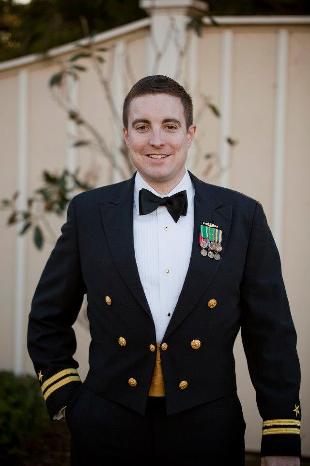 Kevin Ryan stands, looking into the camera and smiling, wearing his military dress jacket with a white button-up shit and black bow tie.