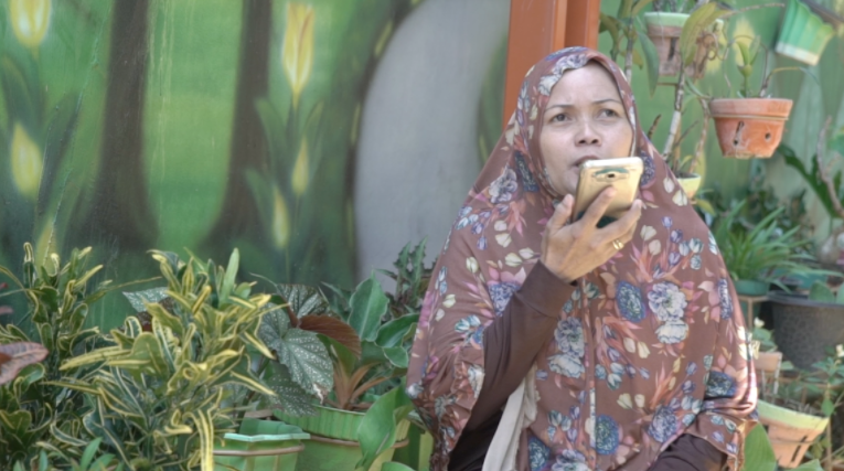 A woman in traditional dress in Indonesia sits facing the camera and talking to her phone. She's surrounded by potted plants.