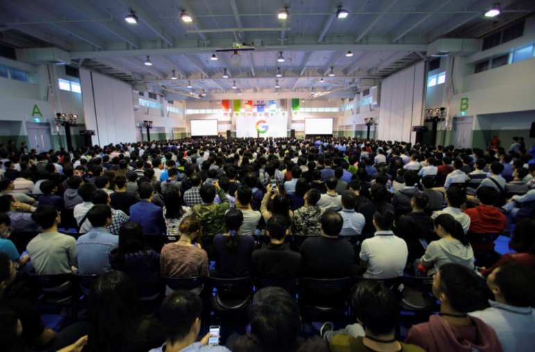 A room full of HTC colleagues looking towards a stage with a Google logo in the background, at their official welcome to Google Taiwan in 2018.
