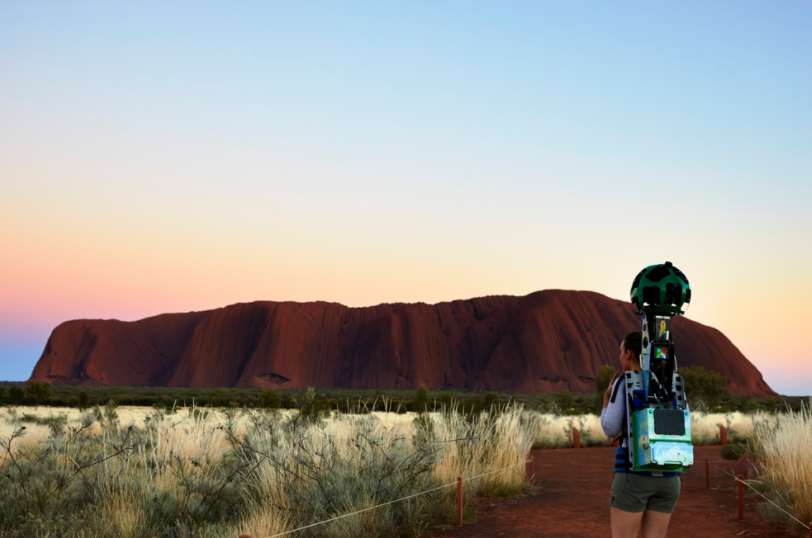 A woman with a camera attached to her backpack looks towards Uluru in the distance, as she films footage for Street View. The sun is setting behind Uluru.