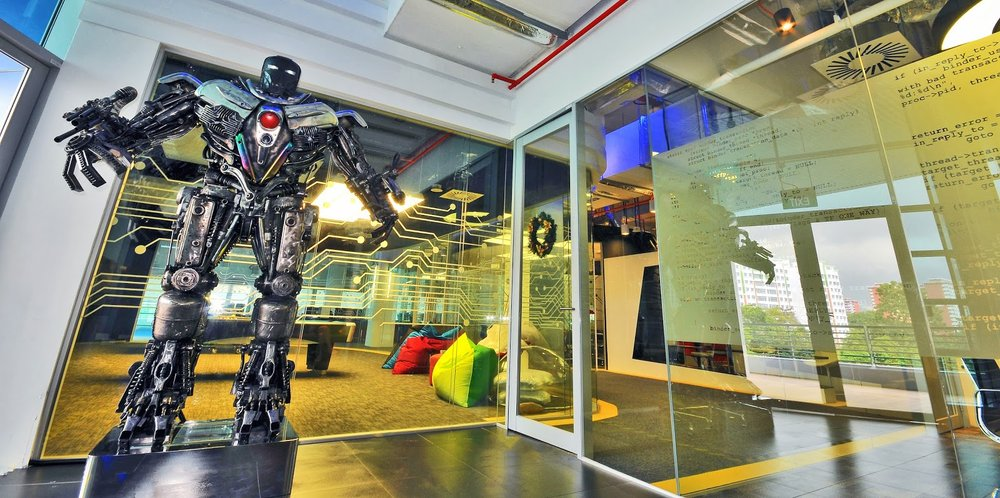 A tall robot-like figurine standing on a plinth in front of the entrance to one of Google's data centers in Singapore. Beanbags and a pool table are visible through the glass office walls.