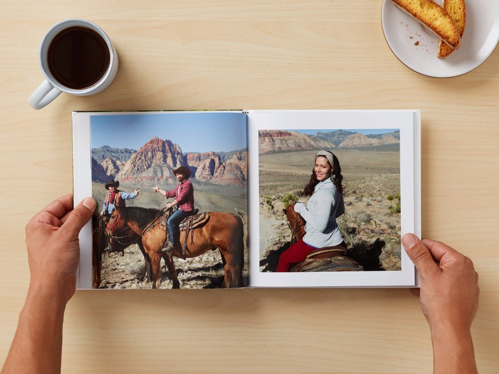 Image of people looking at a photo book from Google Photos.