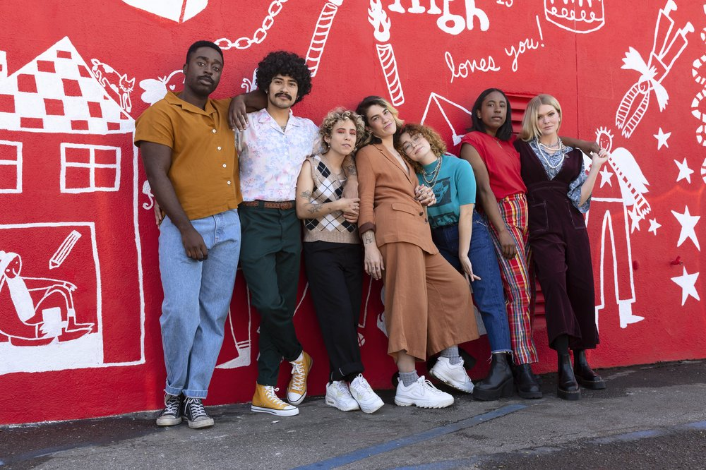A group of seven racially diverse and gender expansive people stand together lovingly in front of a red and white mural at Junior High.