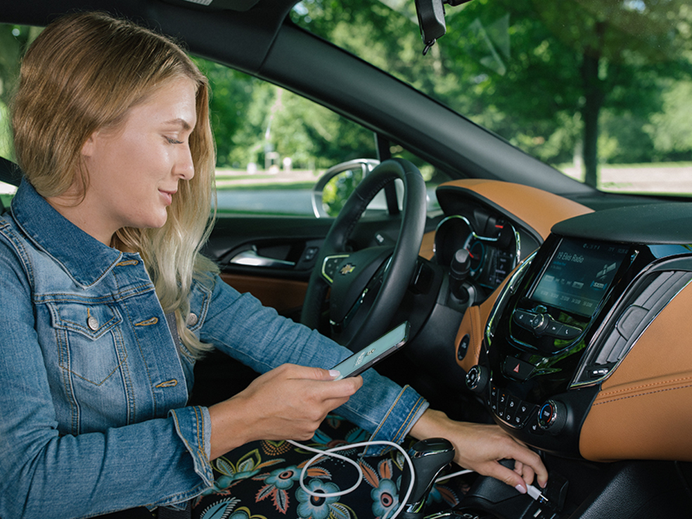 Picture of a woman in a car connecting an Android phone with a cable to a USB port.