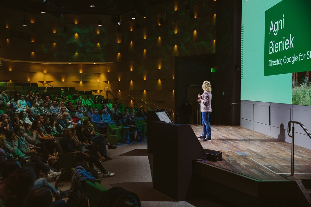 "Agni standing on a stage, addressing an audience. Behind her is a slide that says ""Agni Bieniek, Director Google for Startups."""