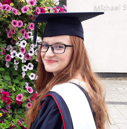 Image shows a young woman with long red hair and glasses looking over her shoulder and smiling at the camera. She's wearing a graduation cap and gown and standing in front of a wall of flowers.