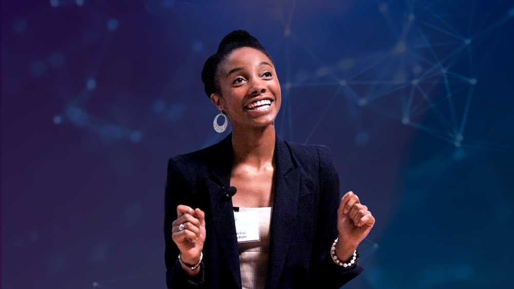 Sarah Murphy Gray is wearing a black blazer and white blouse, smiling broadly and looking out into the audience as she gestures with her hands during a talk at an AI conference.