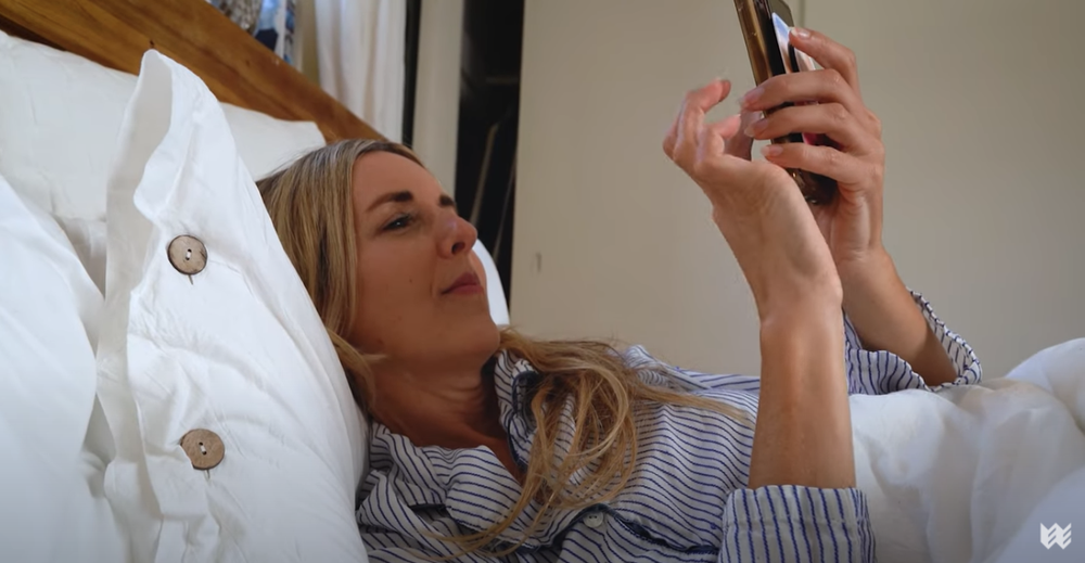 A woman with blonde hair in striped pajamas scrolls through her phone in bed. She is leaning against a white pillow with brown buttons.