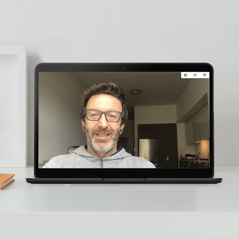 Image of an open laptop screen with a man in a video call, smiling, wearing glasses and a gray sweater.