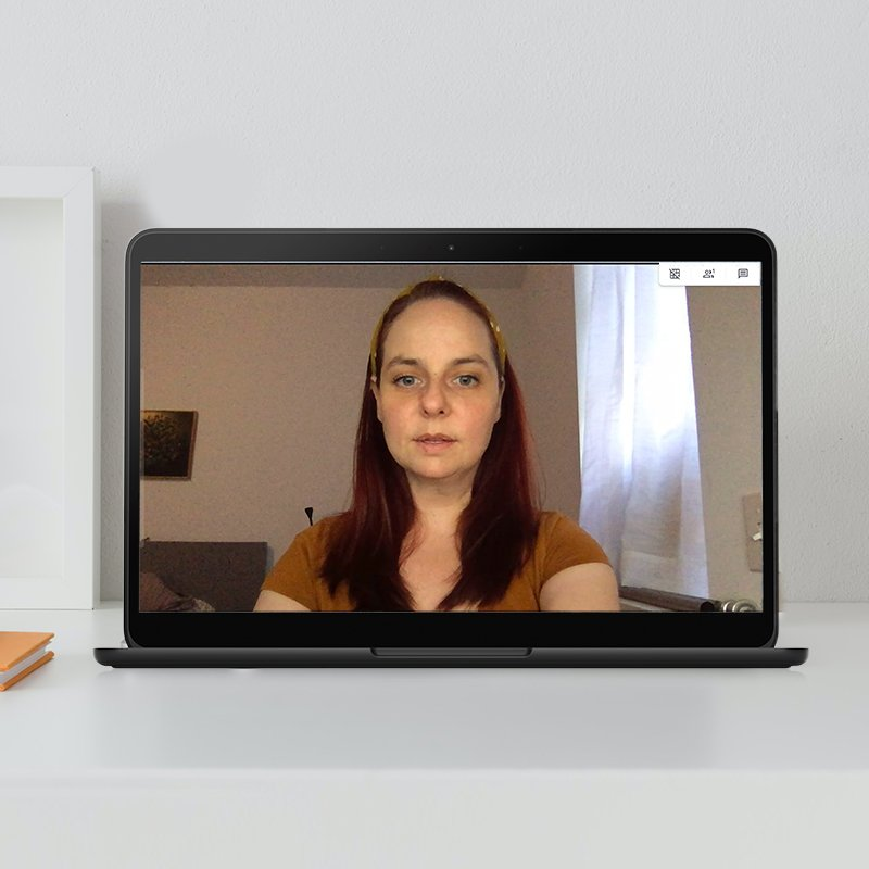 Image of an open laptop screen with a woman in a video call, wearing a brown shirt.