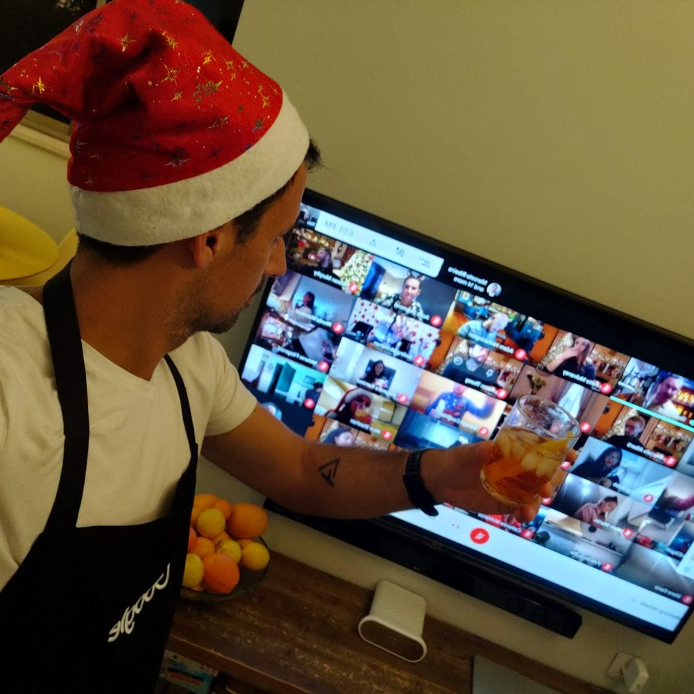 Asaf wears a santa hat and holds up a drink to toast with teammates virtually on a computer