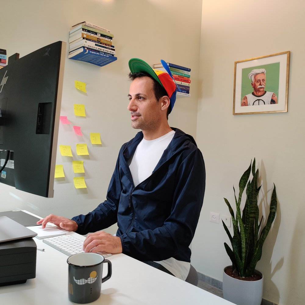 Asaf wearing a Noogler hat while sitting in front of a computer. Around him are books, sticky notes on a wall, a mug, a plant and a painting.