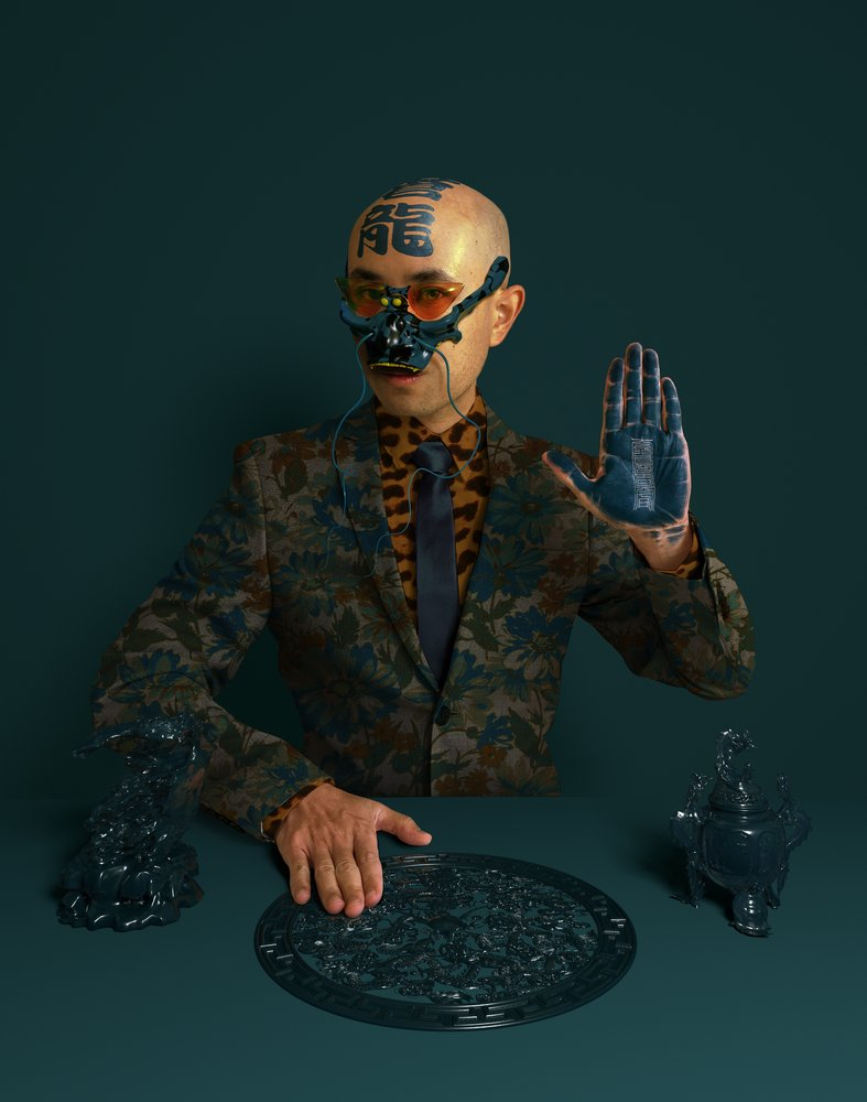 Image showing a person wearing an ornate blue and green suit against a blue green background. They're wearing an intricate mask and holding up their hand, which is painted blue.