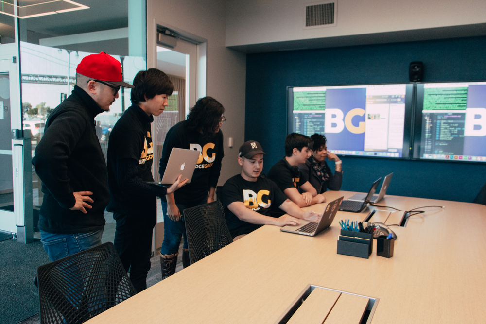 Students at a table gather around a computer