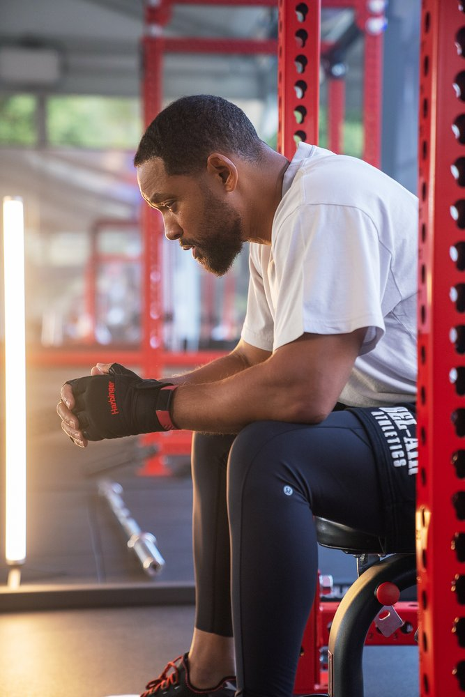 Will Smith resting between sets while sitting on a gym weight bench, wearing Fitbit Charge 4.