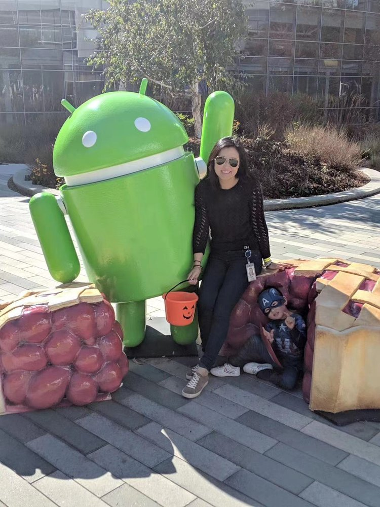 Belle and her son posing on Halloween in front of an Android pie statue.