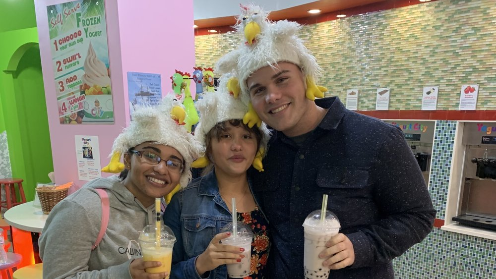 Photo of Deyrel Diaz with his two younger sisters. All are holding boba drinks, looking at the camera, smiling.