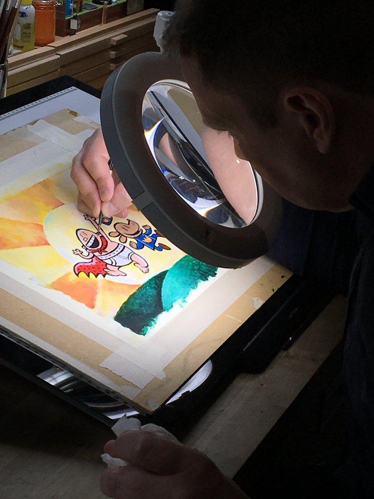 Dav sitting at his workspace drawing.