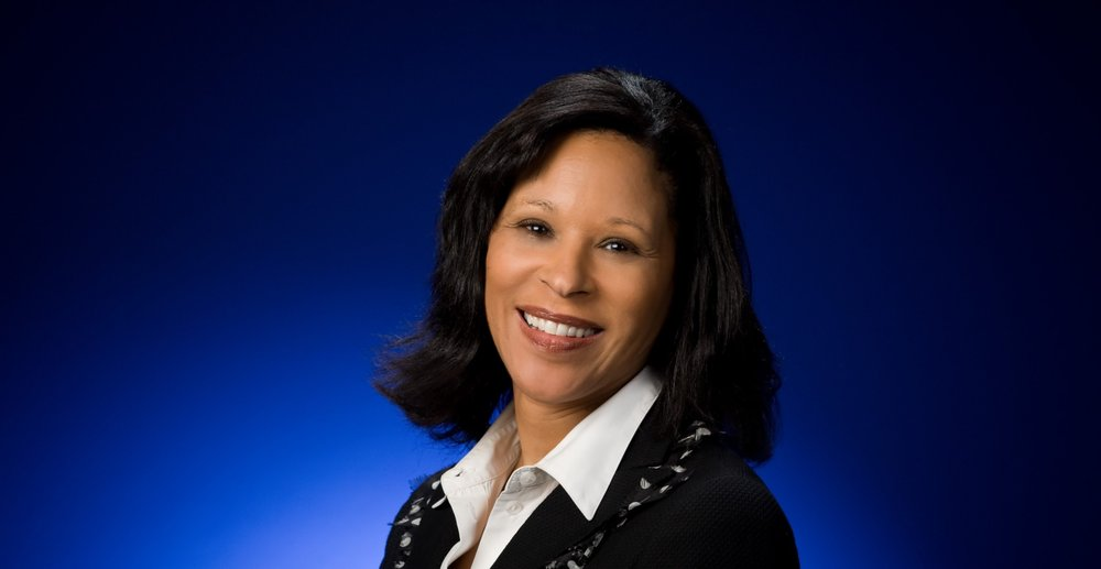 Image shows a headshot of a woman against a blue background; she is looking at the camera and smiling.